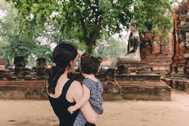 Thailand, Ayutthaya, Mother and daughter looking at a Buddha statue at Wat Mahathat - GEMF02481