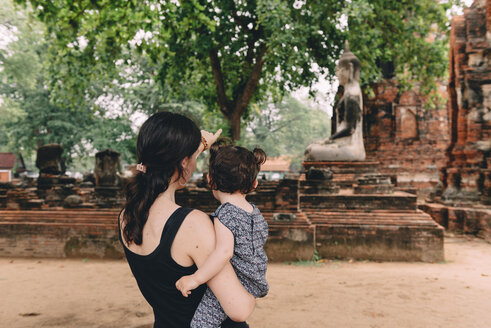 Thailand, Ayutthaya, Mother and daughter looking at a Buddha statue at Wat Mahathat - GEMF02481