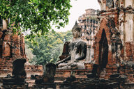 Thailand, Ayutthaya, Buddha statue surrounded by brick pagodes at Wat Mahathat - GEMF02484