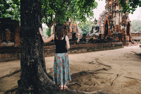 Thailand, Ayutthaya, Woman looking at a Buddha statue at Wat Mahathat - GEMF02487