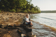 Side view of baby boy sitting on rock at lakeshore against sky during sunset - CAVF53374