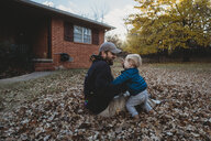 Happy father playing with son while sitting on autumn leaves at yard - CAVF53377