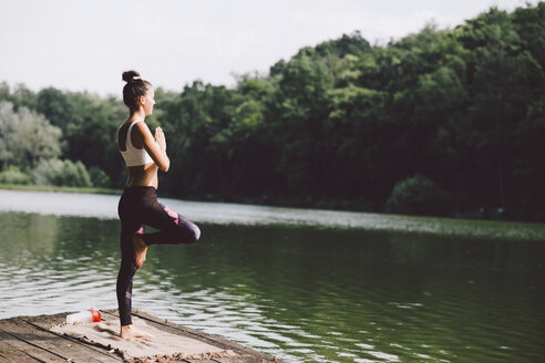 Side view of woman meditating while standing on pier over lake in forest - CAVF53404
