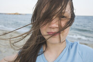 Close-up portrait of girl standing at beach against sky - CAVF53419