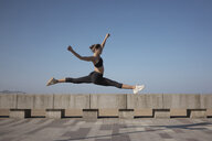 Full length of flexible young woman with legs apart jumping on promenade against clear sky - CAVF53431