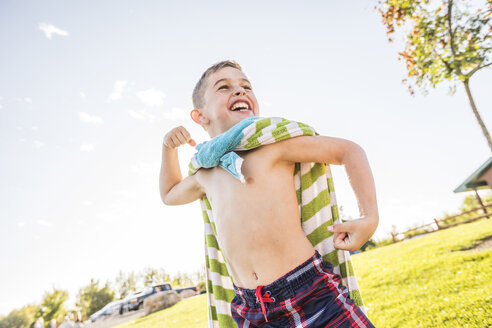 Low angle view of happy shirtless boy with towel flexing muscles while standing against sky at park - CAVF53455