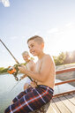 Shirtless happy friends fishing in lake while sitting on pier against sky during sunny day - CAVF53461