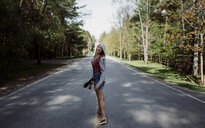 Full length portrait of cheerful woman with skateboard standing on road amidst trees - CAVF53476