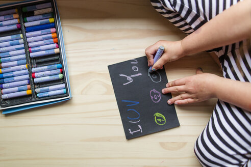 Midsection of girl drawing with colorful crayons on paper while kneeling at home - CAVF53479