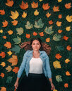 Portrait of smiling young woman in autumn leaves. - INGF06244