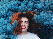 Young and happy redhead woman leaning in blue nature - INGF06274