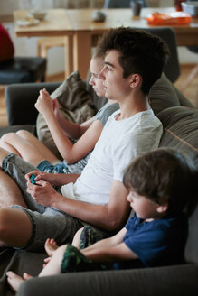 Siblings playing video games on sofa at home. - INGF06319