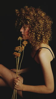 Midsection of a young woman holding flowers - INGF06382