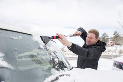 Man cleaning snow from car's windshield during winter - CAVF53505