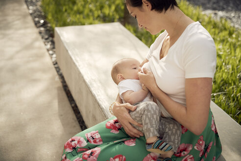 High angle view of mother breastfeeding daughter while sitting on seat - CAVF53526