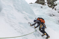 Full length of backpacker ice climbing at White Mountains during winter - CAVF53538