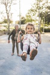 Happy grandmother pushing granddaughter swinging at playground - CAVF53547