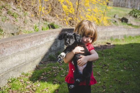 Girl carrying puppy while standing on grassy field at park - CAVF53565