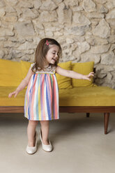Happy girl wearing big shoes while dancing by sofa at home - CAVF53571