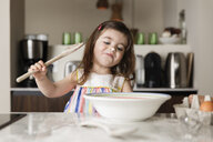 Cute girl preparing food in kitchen island at home - CAVF53574