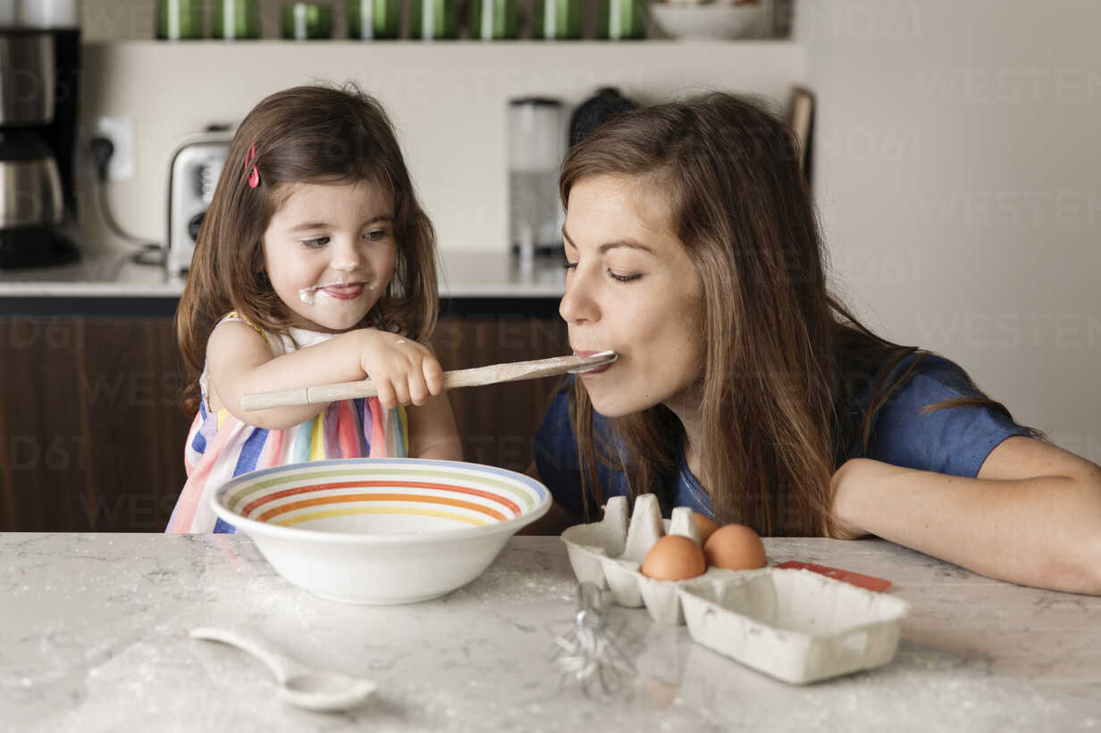 Daughter feeding food to mother in kitchen at home - CAVF53577 - Cavan Images/Westend61
