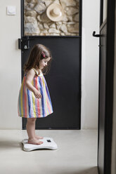 Side view of girl standing on bathroom scale at home - CAVF53580