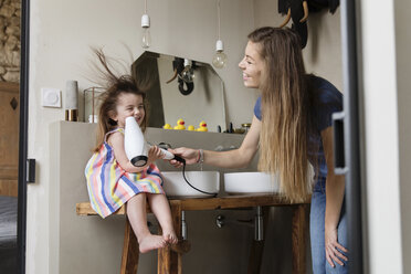 Low angle view of mother drying happy daughter's hair sitting on bathroom sink at home - CAVF53583