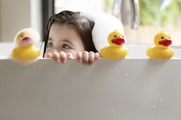 Close-up of girl playing with rubber ducks while bathing in bathtub at home - CAVF53586