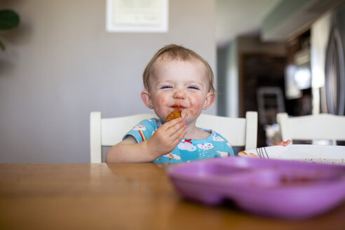 Portrait of baby girl eating food while sitting by table at home - CAVF53634