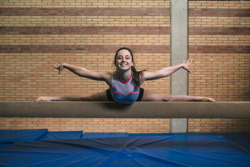 Full length portrait of female gymnast with legs apart and arms outstretched exercising on balance beam against wall at gym - CAVF53649