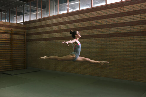 Full length of female gymnast with legs apart and arms outstretched jumping while exercising at gym - CAVF53652