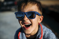 High angle close-up of happy boy wearing sunglasses while sitting outdoors - CAVF53664