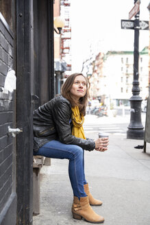 Side view of woman holding coffee while sitting on seat by building in city - CAVF53736