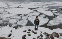 Rear view of boy standing on frozen lake - CAVF53766