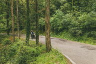 Couple riding motorcycle on road in forest - CAVF53772
