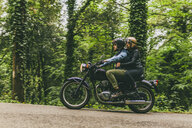 Side view of couple riding motorcycle on road by trees and plants in forest - CAVF53775