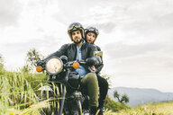 Portrait of couple sitting on motorcycle against sky - CAVF53778