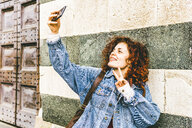 Woman taking selfie while smart phone while standing by wall - CAVF53799