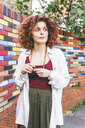 Thoughtful woman looking away while standing against colorful brick wall - CAVF53802