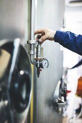 Cropped hand of brewer adjusting pressure gauge at microbrewery - CAVF53814