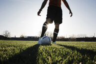 Low section of man playing soccer on grassy field against clear sky during sunset - CAVF53856