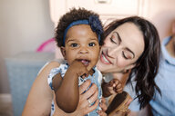 Close-up of happy mother holding daughter at home - CAVF53865