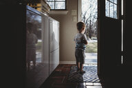 Rear view of silhouette baby boy standing at doorway - CAVF53868
