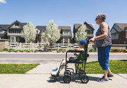 Side view of grandmother pushing grandson on wheelchair on footpath during sunny day - CAVF53889