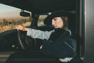 Close-up of thoughtful young woman sitting on driver's seat in off-road vehicle at desert during sunny day - CAVF53892