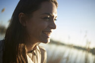 Close-up of smiling young woman looking away against sky during sunset - CAVF53943