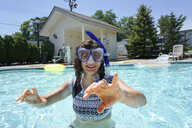Portrait of happy woman wearing snorkel while swimming in pool during sunny day - CAVF53949