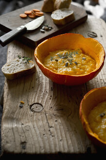 Hokkaido pumpkin soup in pumpkin half garnished with pumpkin seed and thyme - ASF06250