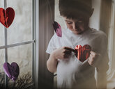 Boy playing with heart shape papers while standing by window at home - CAVF53969