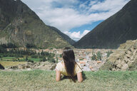 Rear view of female male hiker looking at village while sitting on mountain against sky at Pisac - CAVF53987
